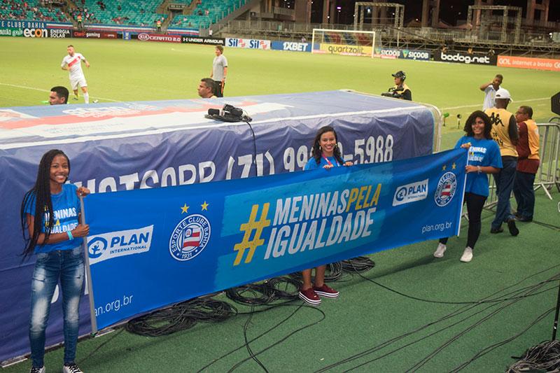 """Meninas negras seguram uma faixa com os dizeres """"Meninas pela Igualdade"""", em um estádio de futebol na Bahia."""