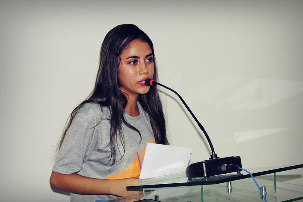 Menina adolescente está discursando em uma tribuna com microfone. A ação faz parte do movimento Meninas Ocupam.