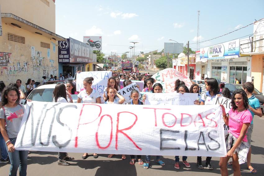 """Meninas adolescentes estão na rua em uma passeata. Na frente, duas meninas seguram uma grande faixa que leva a frase: """"Nós por todas elas"""""""