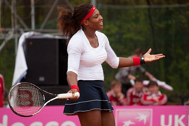 Tenista Serena Williams na quadra de tênis. Ela segura uma raquete na mão direita e acena de braços abertos na quadra.