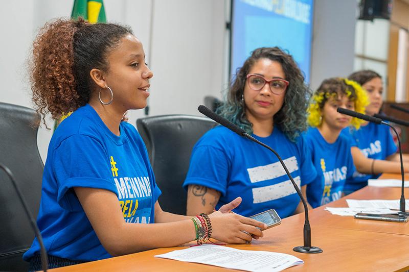 Adolescente negra discursa em uma plenário. AO lado dela, estão uma mulher e mais duas adolescentes.