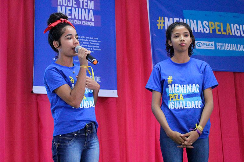 """Duas meninas adolescentes estão em um palco, com fundo vermelho. Elas vestem uma camiseta azul com a frase """"Meninas pela Igualdade"""", da campanha da Plan International Brasil. A menina da esquerda segura um microfone."""
