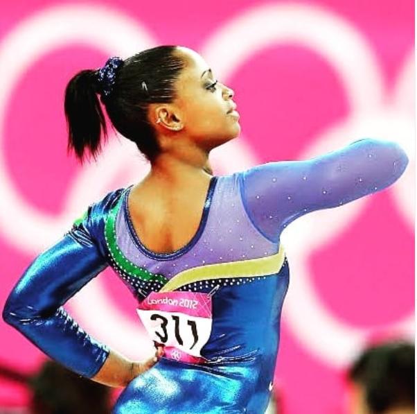A ginasta Daiane dos Santos, mulher jovem negra, está apresentando seus movimentos, em pose imponente. Ela está de costas e veste um colant azul.