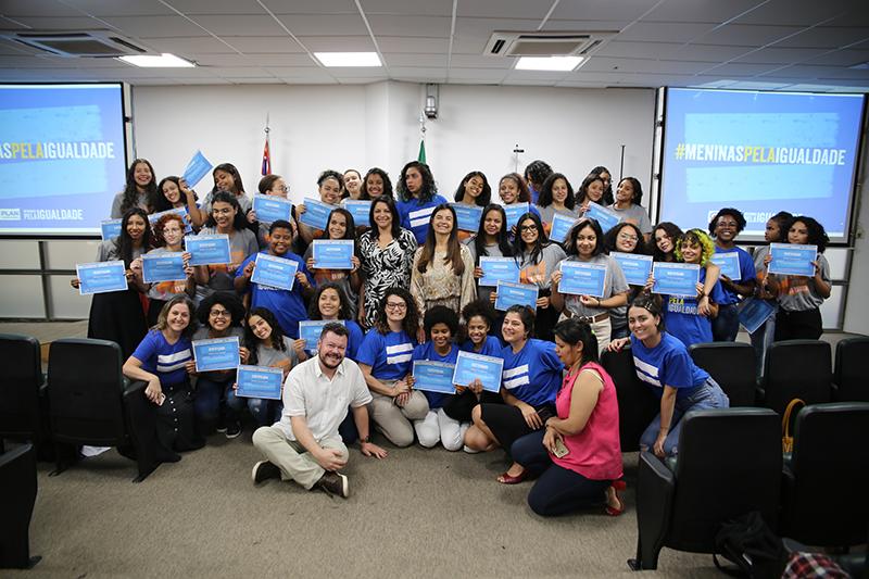 Meninas adolescentes posam para foto com educadores e apoiadores do projeto Escola de Liderança para Meninas, da Plan International Brasil. Elas seguram o certificado de formatura que receberam no evento.