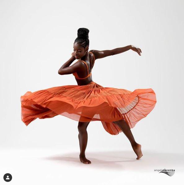 Ingrid Silva, jovem mulher negra, posa como bailaria com uma saia rodada laranja.