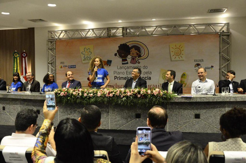 Menina adolescente discursa em um palco ao lado do governador do Estado do Maranhão. A imagem também mostra a plateia com celulares filmando a menina. A ação fez parte do movimento Meninas Ocupam de 2019.