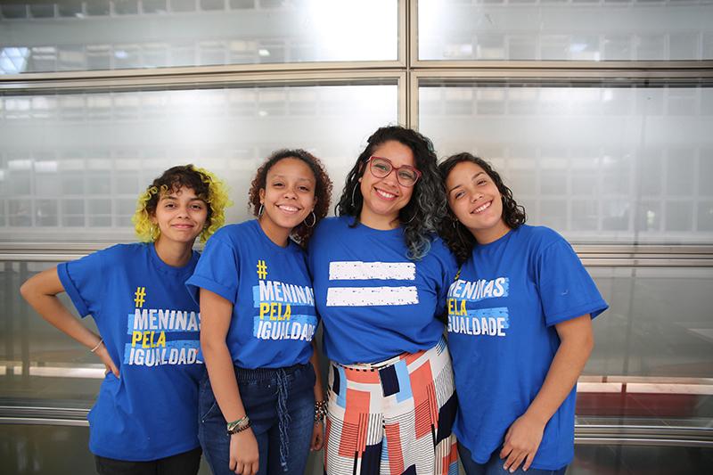 """Três adolescentes meninas posam para foto junto a educadora do projeto Escola de Liderança para Meninas. As meninas vestem uma camiseta azul com a frase """"Meninas pela Igualdade"""", da campanha da Plan International Brasil."""