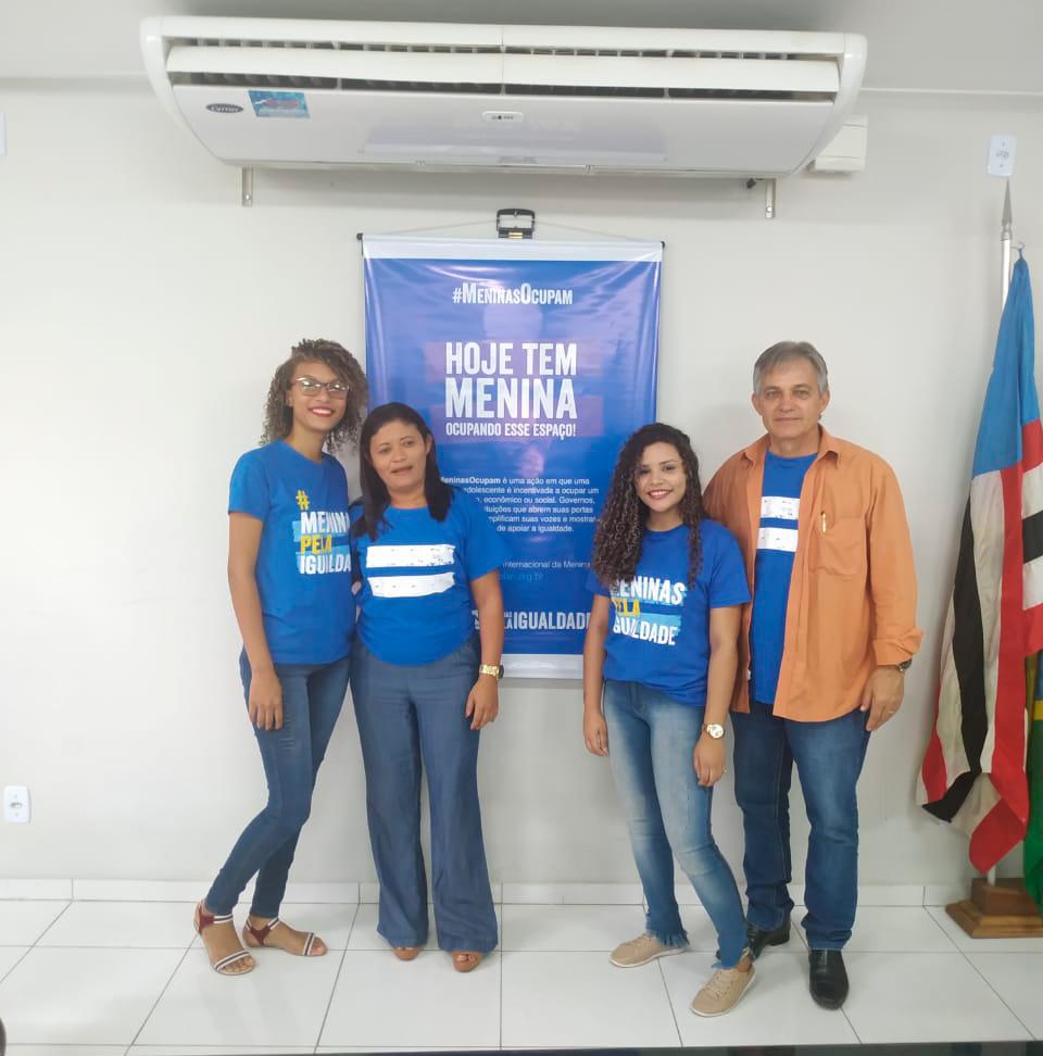 Duas adolescentes posam ao lado do prefeito de Timbiras e da vereadora da cidade. Eles estão em pé em frente a um banner da campanha Meninas Ocupam.