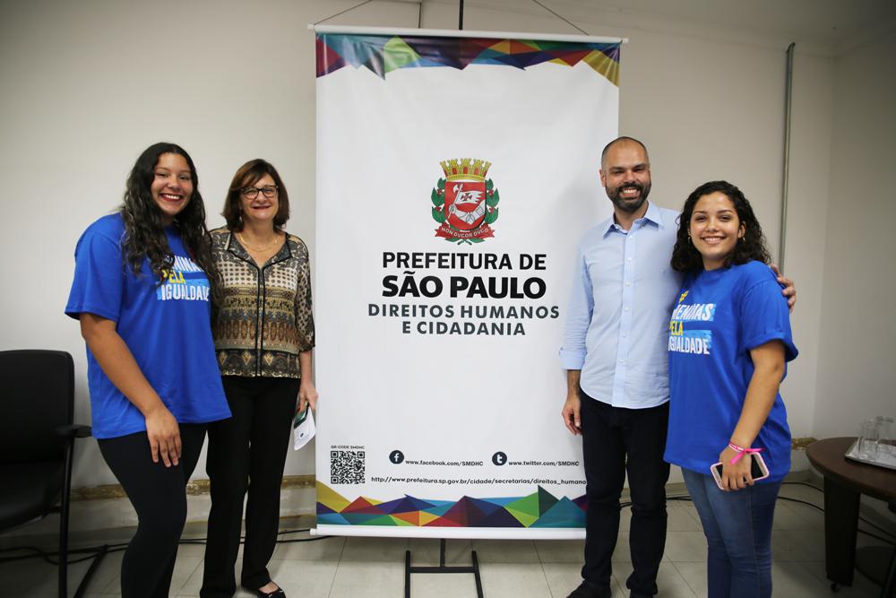 Meninas adolescentes posam com o prefeito de São Paulo e a secretária de Direitos Humanos de São Paulo. O clima é de alegria.