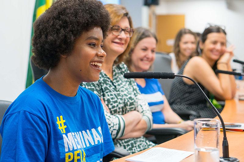 Menina adolescente negra discursa entre mulheres na Assembleia Legislativa de São Paulo