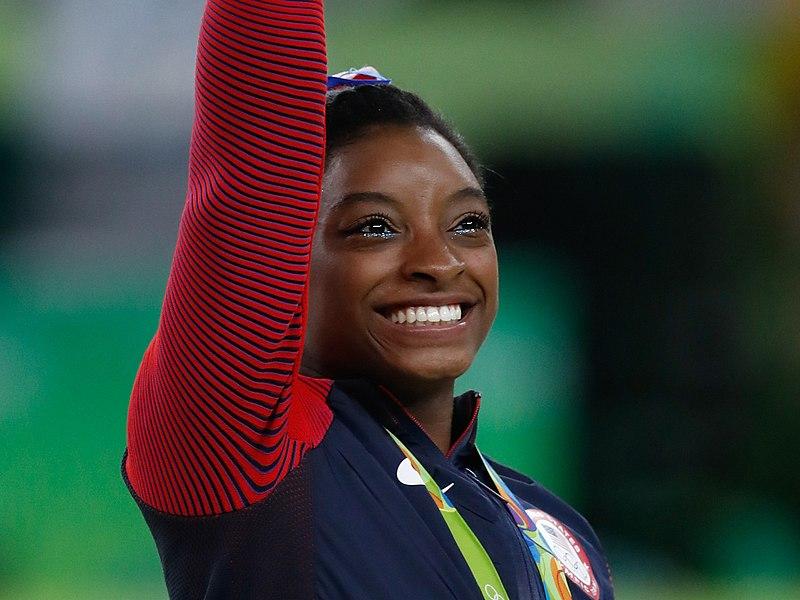 Simone Biles, atleta de ginástica artística e mulher jovem negra, está acenando em clima alegre.