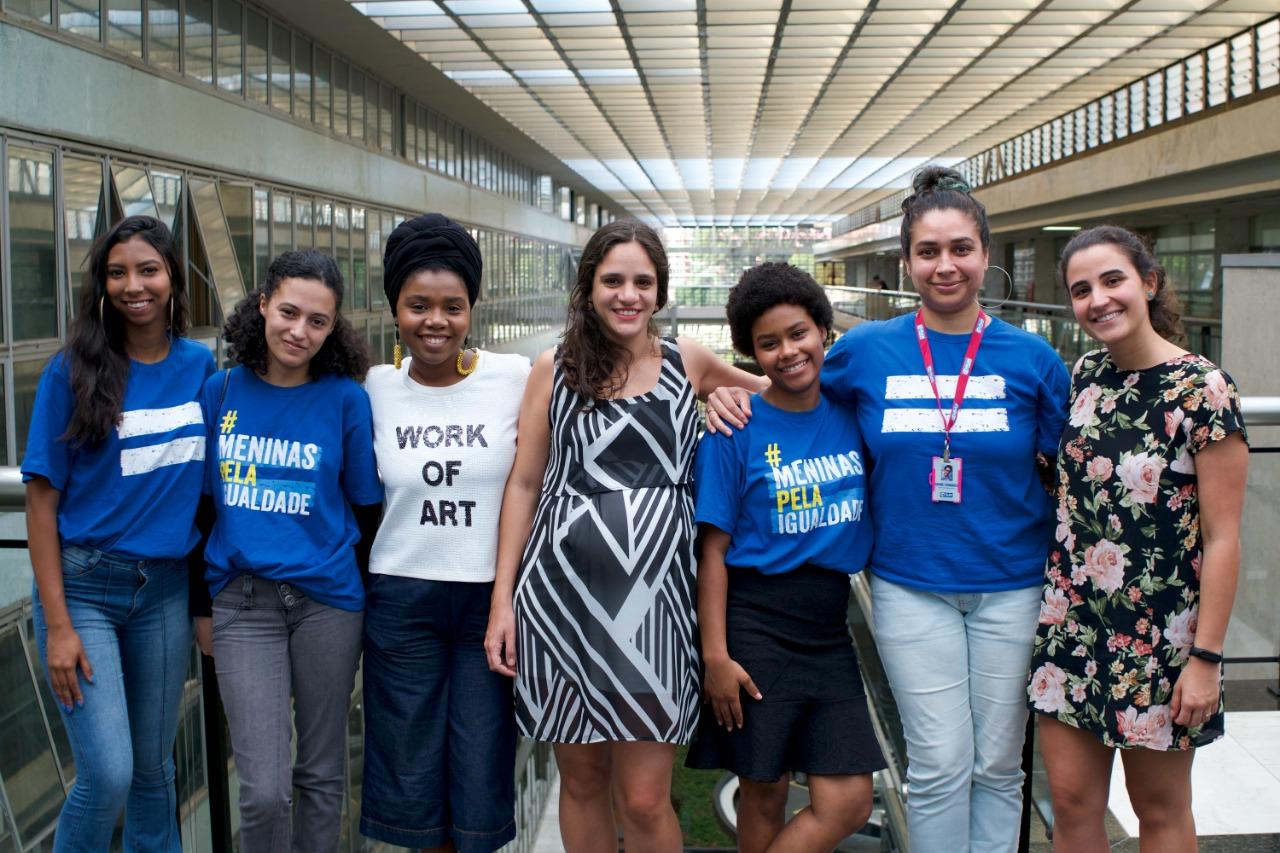Meninas e mulheres posam para foto no ambiente da Assembleia Legislativa do Estado de São Paulo. Todas sorriem.