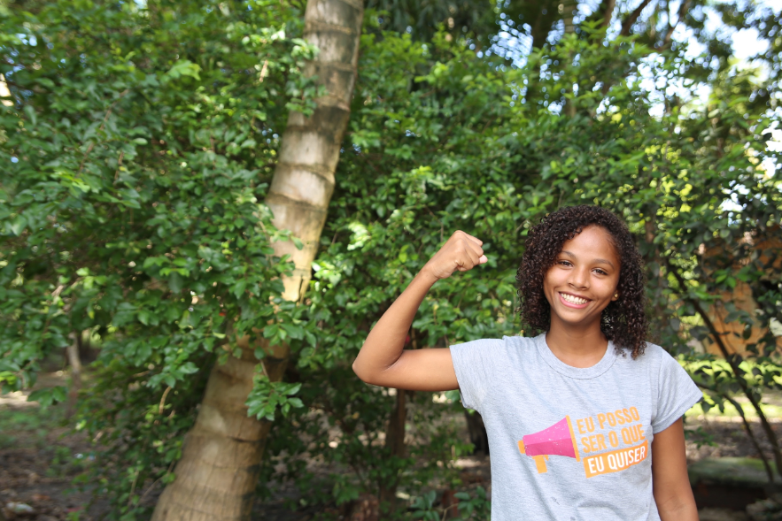 Cassia, uma menina negra, com o punho erguido em frente a uma árvore