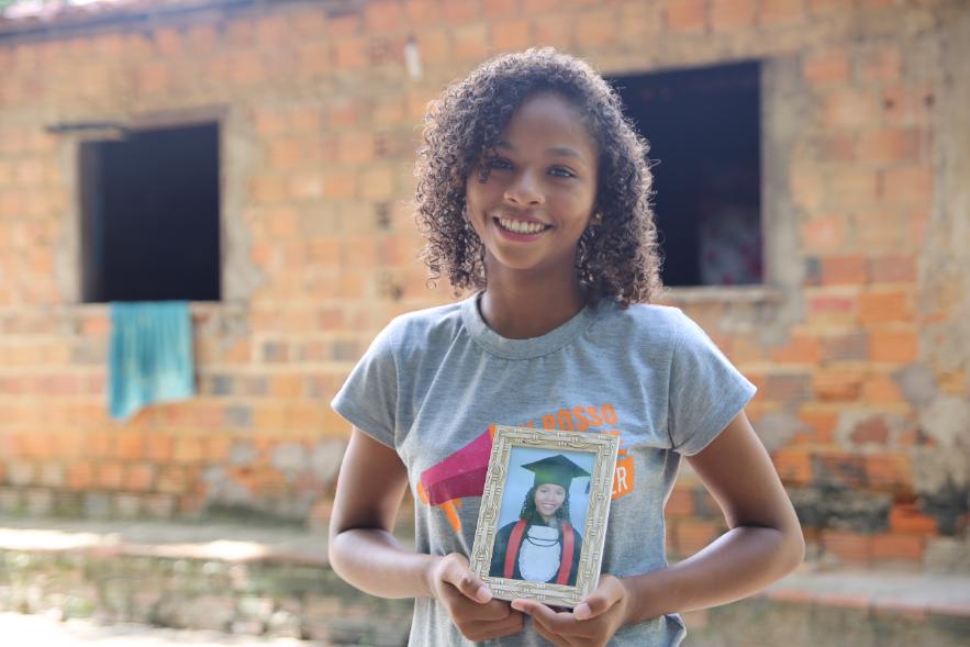 Cassia, uma menina negra, segurando um porta retrato e frente a sua casa