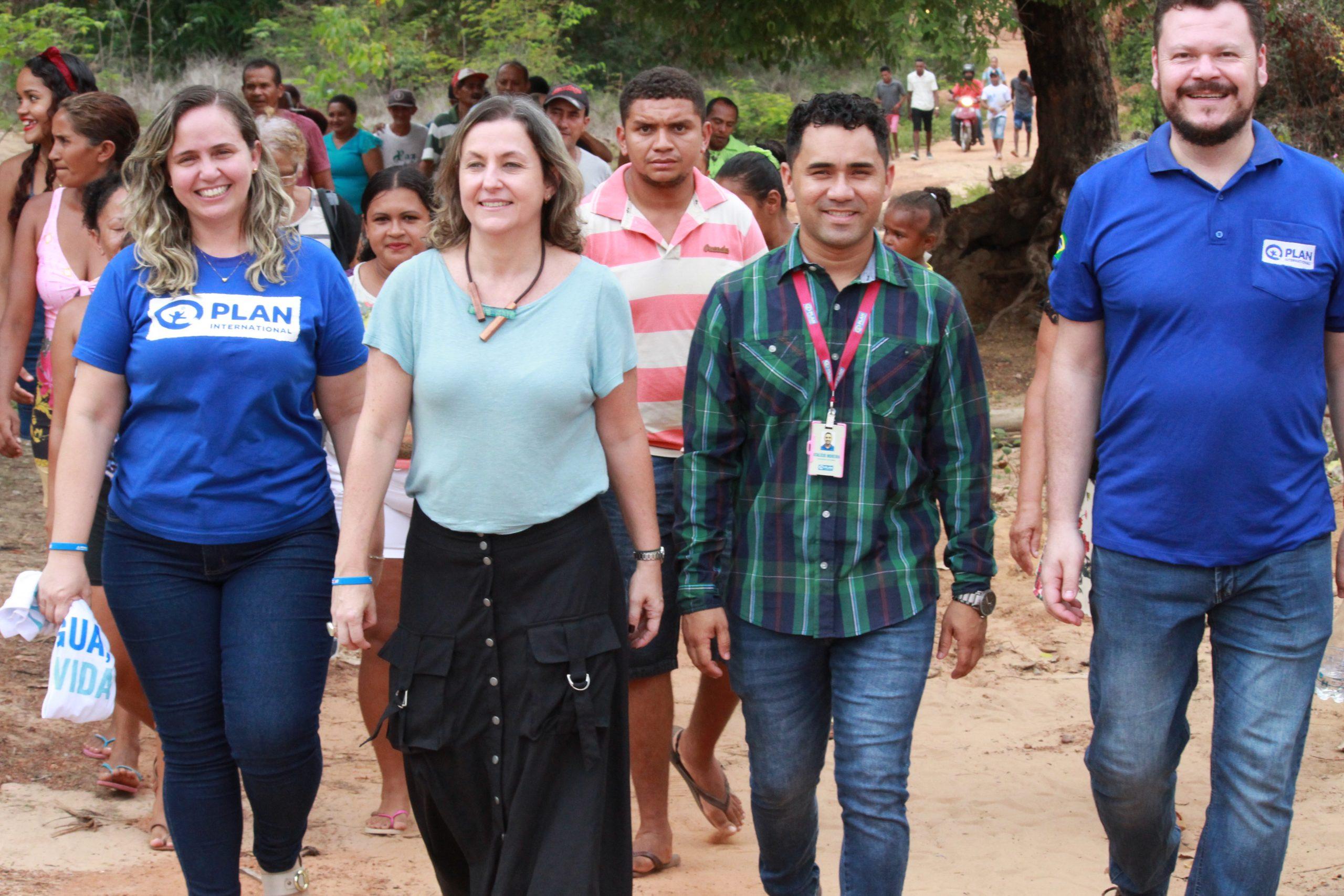 Duas mulheres e dois homens caminham lado a lado. Atrás deles, há algumas pessoas caminhando também. Todos sorriem.