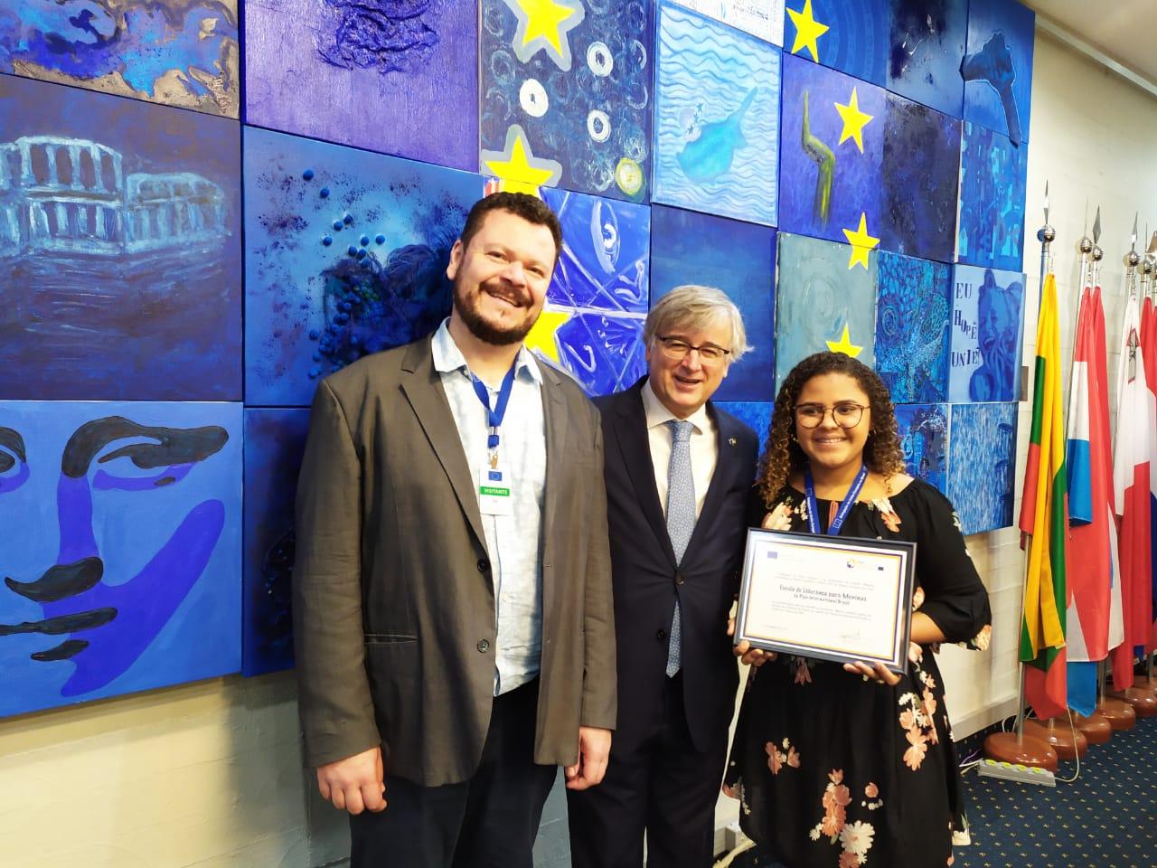 Dois homens e uma jovem posam para foto. A jovem segura um certificado da premiação de direitos humanos da União Europeia, concedido à Plan International Brasil.