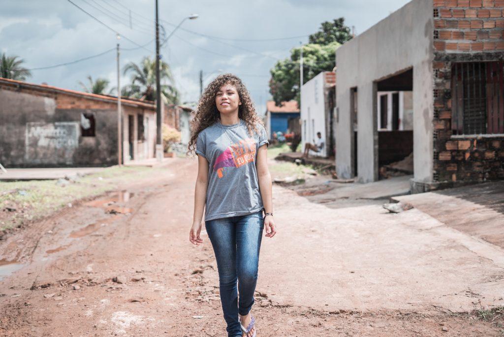 Menina jovem andando em uma rua que não possui asfalto. Ela está vestindo uma camiseta com os dizeres: Eu posso ser o que quiser.