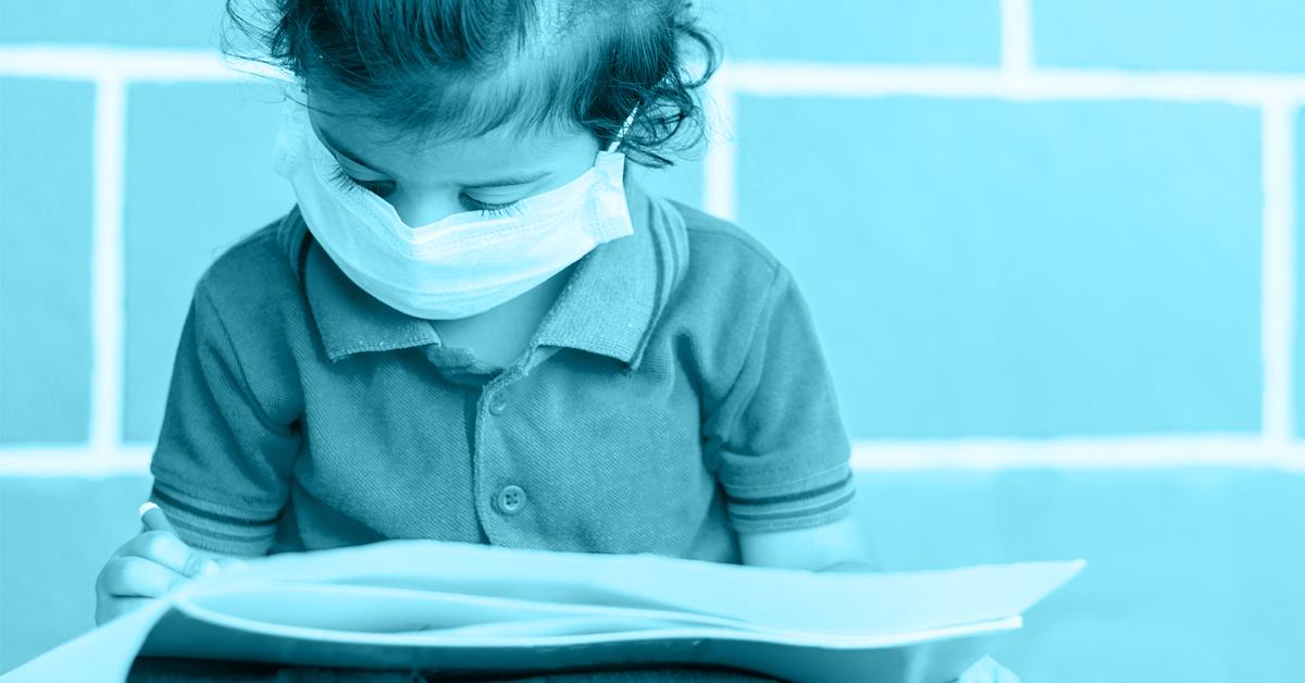 Criança com máscara lendo um livro