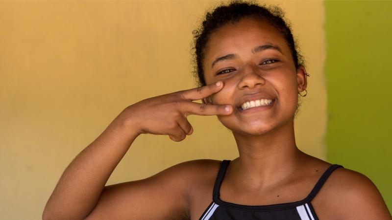 meninas faz sinal de igualdade com as mãos no rosto
